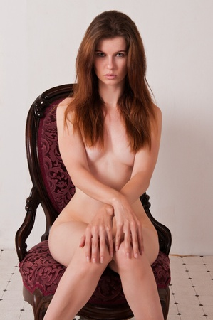Pretty brown haired girl nude in an antique chair Stock Photo - 9711953