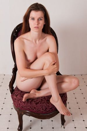 Pretty brown haired girl nude in an antique chair Stock Photo - 9711961