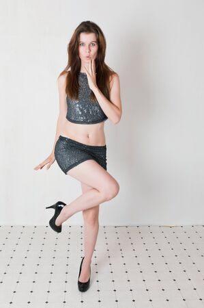 brown haired girl: Pretty brown haired girl in a skimpy sequined blouse and skirt Stock Photo