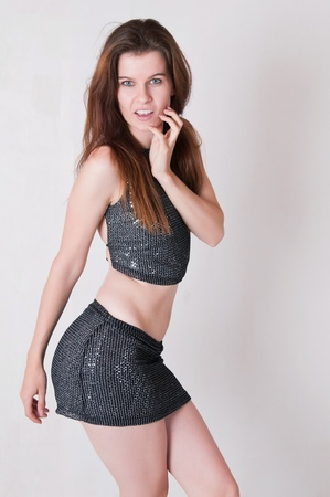 skimpy: Pretty brown haired girl in a skimpy sequined blouse and skirt Stock Photo