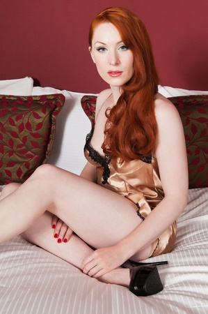 Lovely pale redhead in bed in a gold chemise photo