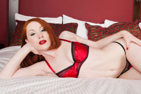 Lovely pale redhead in bed in red and black lingerie photo