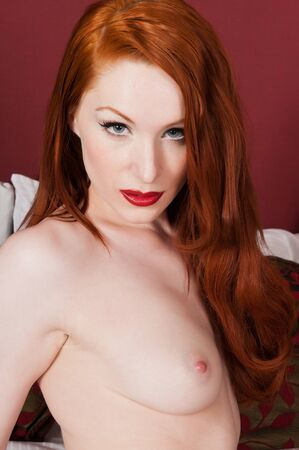 Lovely pale redhead topless in bed Stock Photo - 9877469