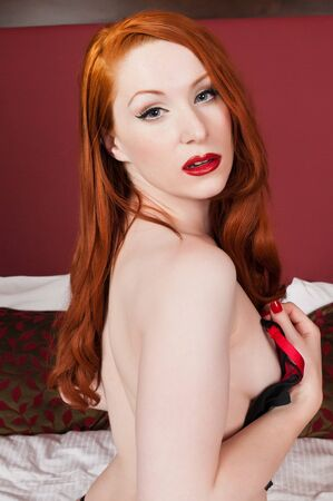 undressing girl: Lovely pale redhead in bed in black and red Stock Photo