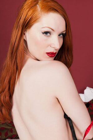 undressing woman: Lovely pale redhead in bed in black and red Stock Photo