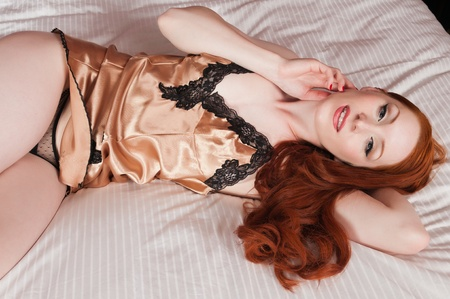 chemise: Lovely pale redhead in bed in a gold chemise Stock Photo