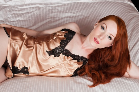 Lovely pale redhead in bed in a gold chemise Imagens