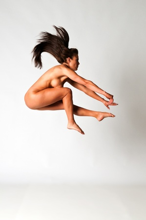 Athletic nude brunette demonstrating gymnastic skills