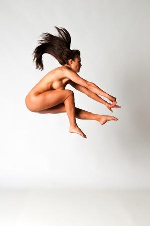 Athletic nude brunette demonstrating gymnastic skills
