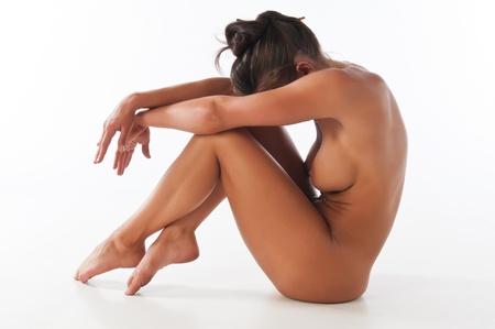 female nudity: Athletic nude brunette demonstrating gymnastic skills