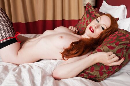 Lovely pale redhead lying nude in bed photo