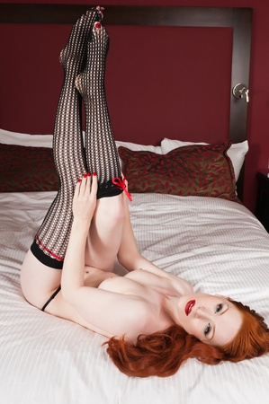 Lovely pale redhead lying topless in bed photo