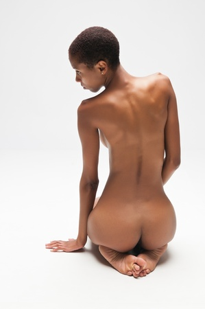 Slender young black woman posing nude on white