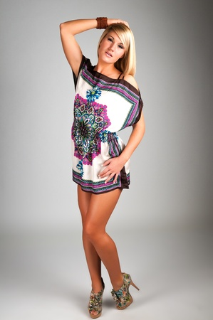 petite girl: Lovely young blonde in a short tapestry dress Stock Photo