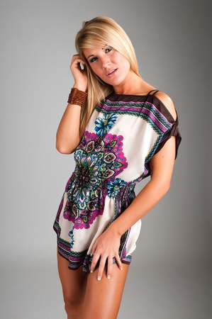 Lovely young blonde in a short tapestry dress photo