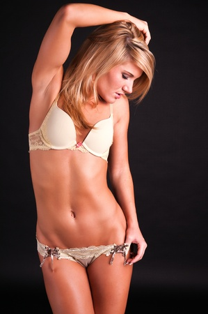 Lovely young blonde dressed in yellow lingerie photo