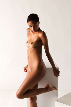 afro american nude: Slender young black woman posing nude on white