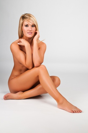 nude blond: Lovely young blonde woman nude against white Stock Photo