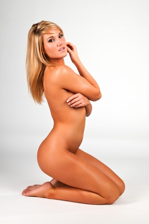 Lovely young blonde woman nude against white photo
