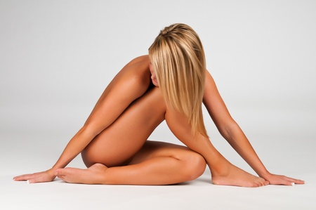 Lovely young blonde woman nude against white Stock Photo