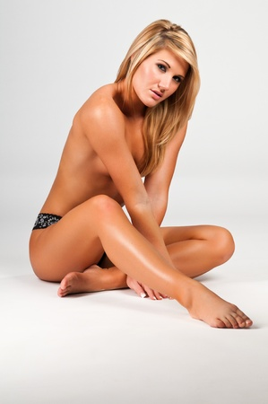 Lovely young topless blonde in black panties photo