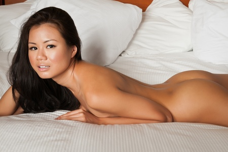 naked girl black hair: Pretty Singaporean woman lying nude in bed