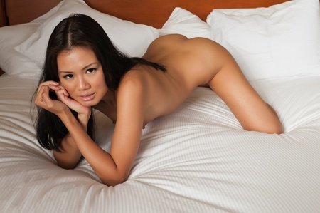 nudity girl: Pretty Singaporean woman lying nude in bed