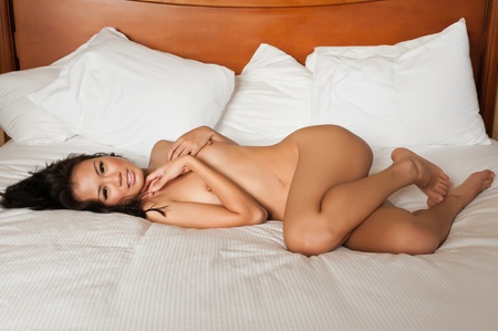 Pretty Singaporean woman lying nude in bed Stock Photo - 10001755