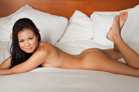 Pretty Singaporean woman lying nude in bed photo