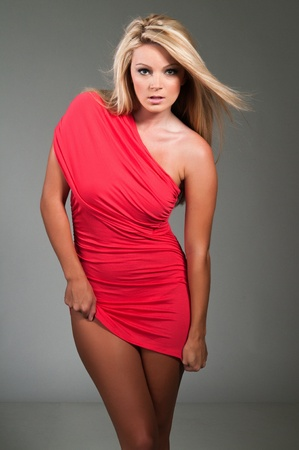 Beautiful curvy blonde dressed in a tight red dress photo