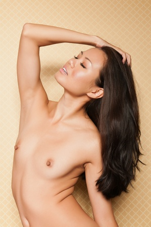 asia nude: Pretty Singaporean woman sitting nude against a bedroom wall