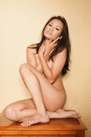 Pretty Singaporean woman sitting nude on a bedroom nightstand Stock Photo - 10001432