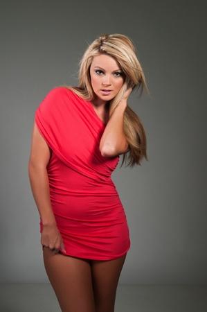 voluptueuse: Belle blonde sinueuse v�tue d'une robe serr�e rouges