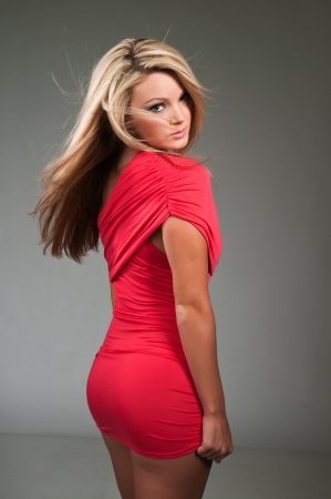 タイトな赤いドレスに身を包んだ美しい曲線ブロンド