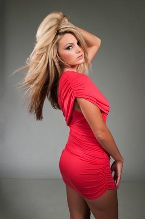 voluptuosa: Hermosa rubia curvil�nea vestida con un vestido rojo ajustado Foto de archivo
