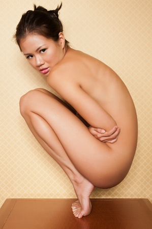 undressed young: Pretty Singaporean woman sitting nude on a bedroom nightstand Stock Photo