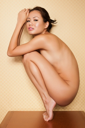 Pretty Singaporean woman sitting nude on a bedroom nightstand Stock Photo - 10084773