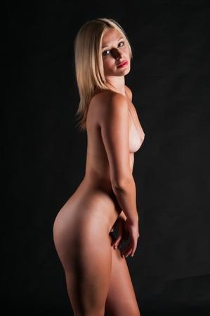 femme se deshabille: Belle blonde nue debout dans l'ombre Banque d'images
