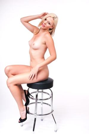 Beautiful tall nude blonde sitting on a barstool Stock Photo - 10084784