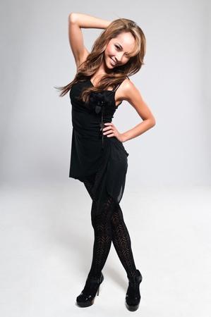 Schöne schlanke Brünette im schwarzen Kleid