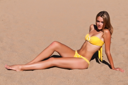 is slender: Pretty young brunette in a yellow bikini