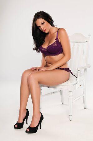 mujeres sentadas: Bastante joven morena vestida con lencería color púrpura