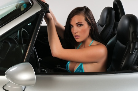 Pretty young brunette in a convertible sports car