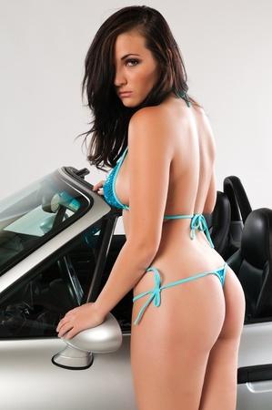 voluptueuse: Jolie jeune brune se penchant sur une voiture sport d�capotable