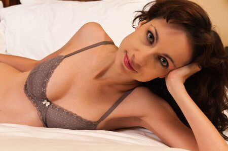 undergarments: Pretty young brunette in bed in mauve lingerie