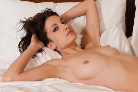 Pretty young brunette lying topless in bed