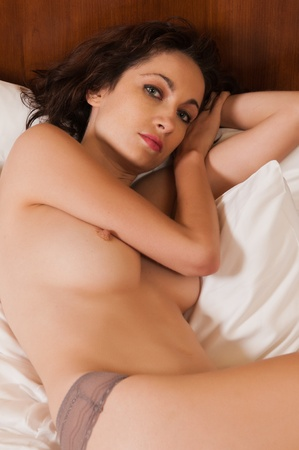 Pretty young brunette lying topless in bed Stock Photo - 10352046