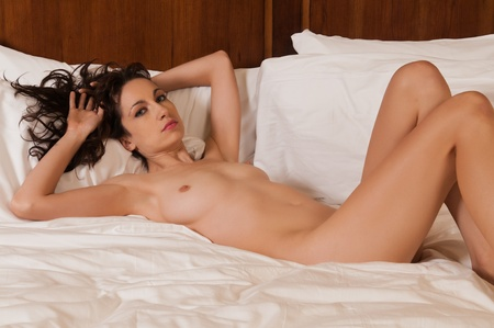 nude in bed: Pretty young brunette lying nude in bed