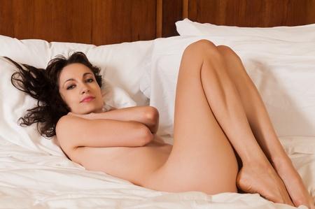 girl naked: Bastante joven morena desnuda acostada en la cama