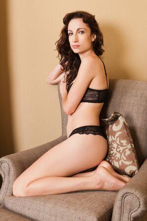 Pretty brunette in an armchair in black lingerie photo
